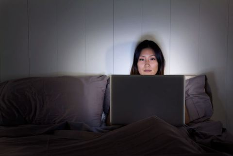 kvinna on computer in bed