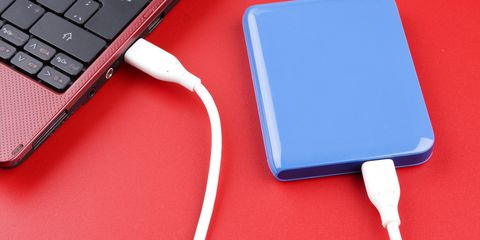 สีน้ำเงิน external hard drive plugged into red laptop