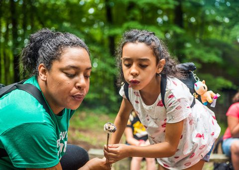 en Girl Scout of the USA and her troop leader blow on a roasted marshmallow at a campout.