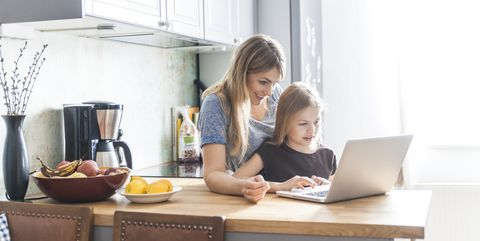 แม่ and daughter using laptop in kitchen